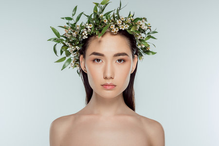 naked asian girl in floral wreath, isolated on grey