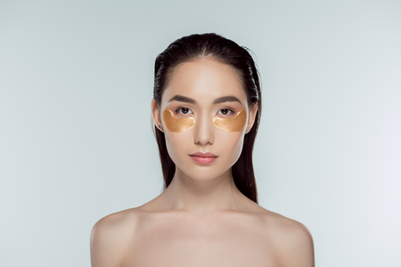 beautiful asian girl with golden eye patches, isolated on grey Stock Photo