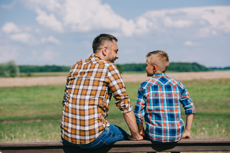 back view of father and son sitting on fence and smiling each other at farm