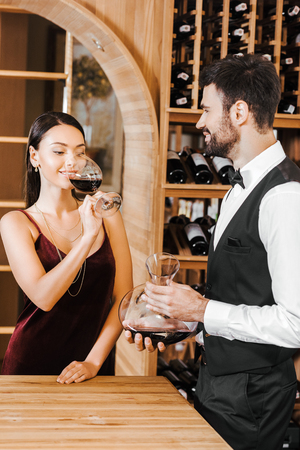 wine steward holding decanter of wine in front of female client at wine store Stock Photo