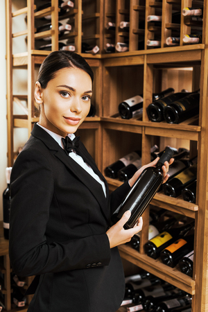 beautiful female wine steward holding bottle and looking at camera at wine store Stock Photo