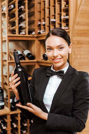beautiful female wine steward holding bottle at wine store