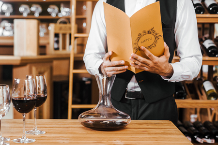 cropped shot of sommelier with wine card standing in front of table with decanter and glasses at wine store