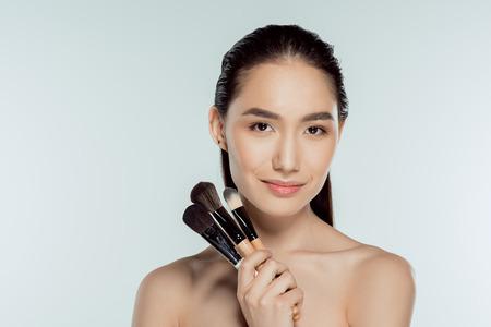 beautiful asian girl holding makeup brushes, isolated on grey