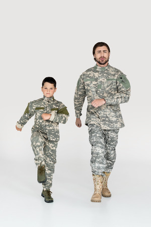 father and son in military uniforms marching and looking at camera on grey background