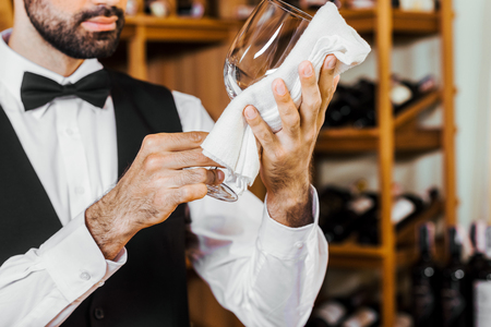 cropped shot of young wine steward wiping glass at wine store