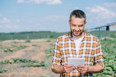 Guapo agricultor sonriente con tableta digital mientras está de pie en el campo