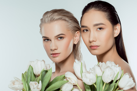 multicultural girls posing with white tulip flowers, isolated on grey
