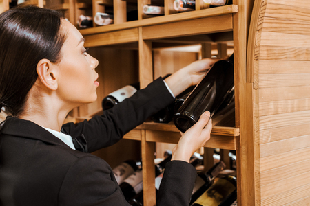 attractive female wine steward taking bottle from shelf at wine store Stock Photo