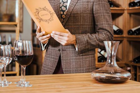 cropped shot of man in tweed jacket reading menu at wine store