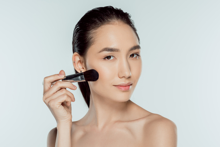 asian girl applying blushes with cosmetic brush, isolated on grey