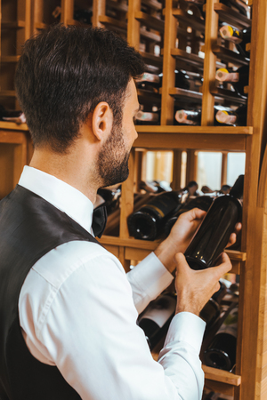 handsome young sommelier taking bottle from shelf at wine store Stock Photo