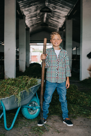 happy boy in checkered shirt standing with pitchfork and smiling at camera in stall Stock Photo