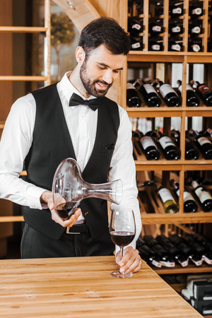 handsome young sommelier pouring wine from decanter at wine store Stock Photo