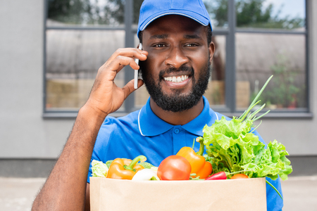 smiling african american delivery man holding paper bag with vegetables and talking by smartphone 免版税图像
