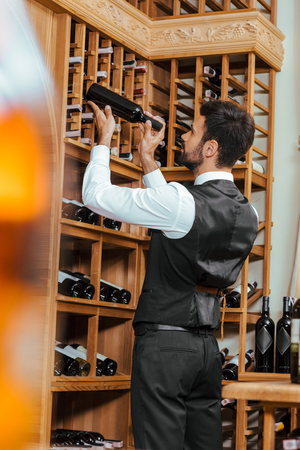 handsome young sommelier putting bottle on shelf at wine store Stock Photo