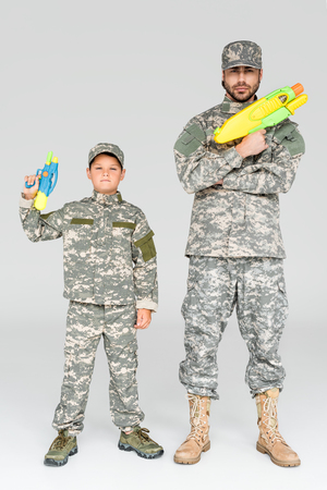 father and son in military uniforms with toy water guns on grey background Imagens