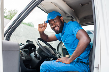 african american delivery man greeting and touching cap in car Stock Photo - 107626321