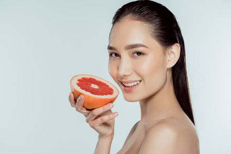 smiling asian girl holding grapefruit, isolated on grey Stock Photo