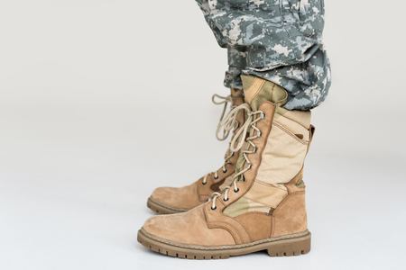 partial view of male soldier in camouflage clothing and boots on grey background Banco de Imagens