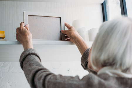 partial view of senior lady taking empty photo frame from bookshelf at home Фото со стока