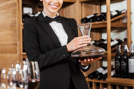 cropped shot of smiling female wine steward holding decanter at wine store