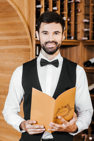 handsome young sommelier in vest and bowtie holding wine card at store