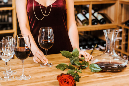cropped shot of woman in red dress with wine glasses and rose at wine store