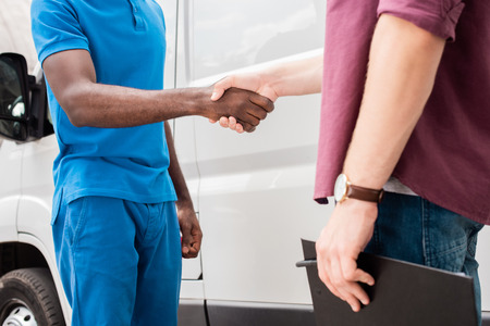 cropped image of multicultural courier and client shaking hands near van Stock Photo