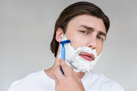 portrait of attractive man with foam on face and razor shaving beard on grey backdrop