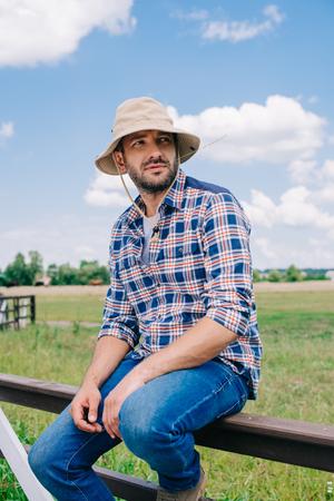 Pensativo agricultor de mediana edad con sombrero de Panamá sentado en el cerco y mirando lejos en el campo
