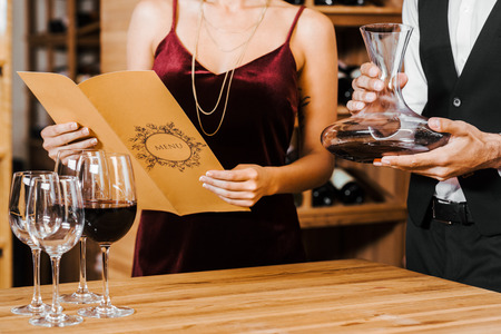 cropped shot of wine steward holding decanter while client reading menu list at wine store Stock Photo