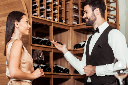wine steward showing wine storage to beautiful young woman
