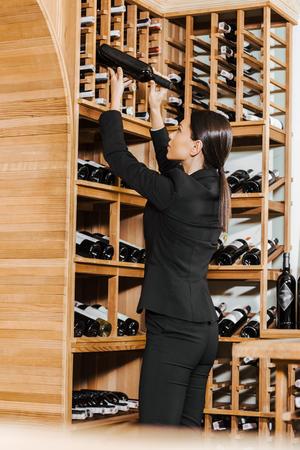 beautiful female wine steward taking bottle from shelf at wine store Stock Photo