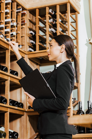 beautiful female wine steward with notebook counting bottles on shelves at wine store Stock Photo