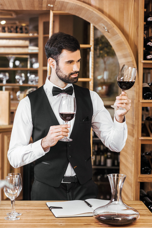 confident young sommelier examining color of wine at wine store Stock Photo