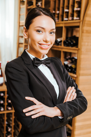 smiling female wine steward with crossed arms looking at camera at wine store