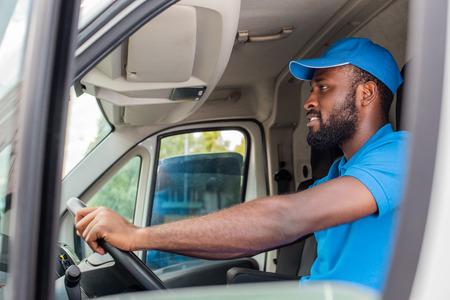 side view of african american delivery man driving van Stock fotó