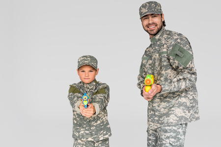 portrait of family in military uniform with water guns in hands isolated on grey