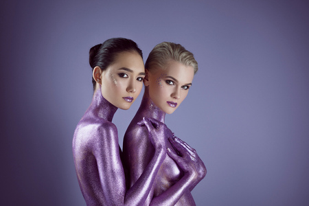 multicultural naked women in purple glitter hugging each other, isolated on violet Foto de archivo