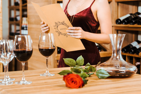 cropped shot of woman in red dress reading menu card at wine store Stockfoto