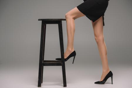 Imagen recortada de la empresaria en zapatos con tacones de pie con la pierna en la silla sobre fondo gris