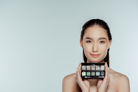attractive asian girl holding palette with eyeshadows, isolated on grey