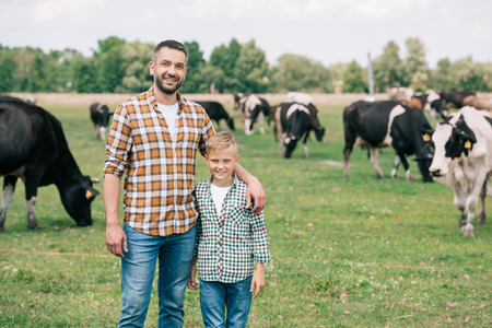 father and son smiling at camera while standing near grazing cattle at farm Banco de Imagens - 107653829