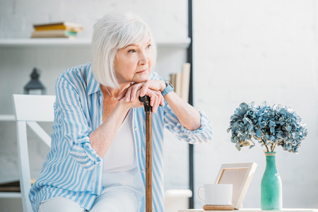 portrait of thoughtful senior woman with walking stick looking away at home Stock Photo