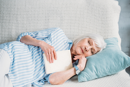 portrait of senior woman with book sleeping on sofa at home 版權商用圖片