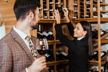 female wine steward taking bottle from shelf for client at wine store Stock Photo