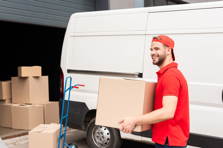 smiling delivery man in uniform with cardboard box standing near white van in street Banco de Imagens