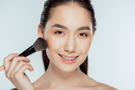 beautiful asian woman applying powder with cosmetic brush, isolated on grey Stock Photo