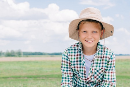 adorable child in panama hat smiling at camera on farm